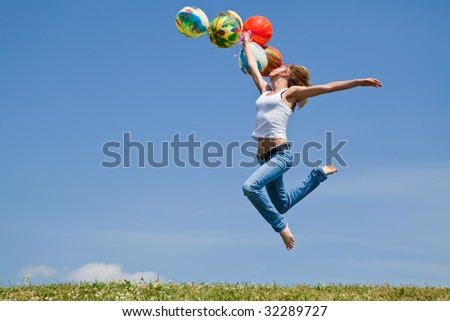 Girl jumps on a green grass with balloons in a hand - stock photo