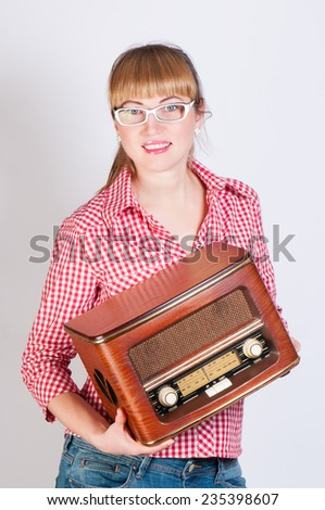 girl keeps in a plaid shirt stylized the semi-antique radio receiver - stock photo