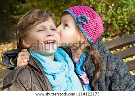 Girl kissing a boy on a bench in park - stock photo