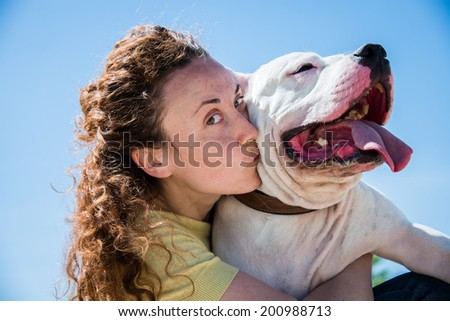 Girl kissing dog breed Staffordshire Terrier - stock photo