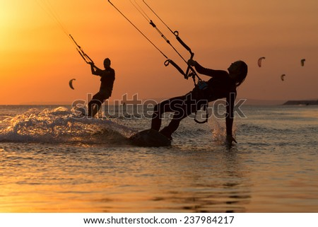 Girl kiter riding on a beautiful background of spray and colourful sunset of Black sea - stock photo
