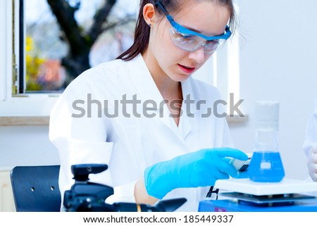 girl laboratory assistant checks samples in a medical lab - stock photo