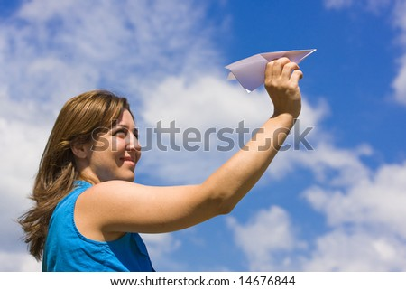 Girl launching  a paper plane - stock photo