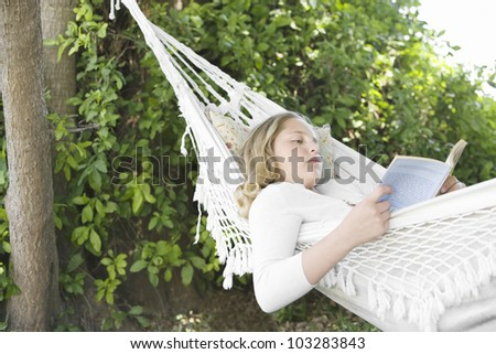 Girl laying down on a hammock in the garden, reading a book. - stock photo