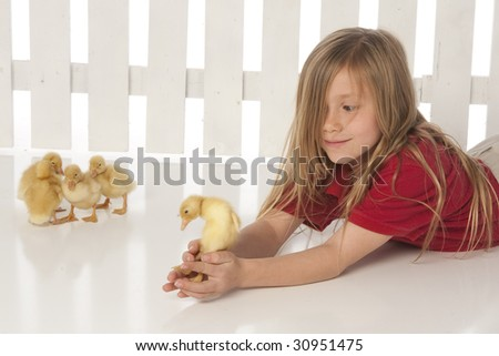 Girl laying with ducklings - stock photo