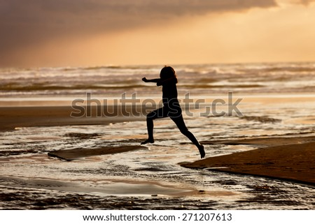 Girl leaps into the water on Nye Beach that flows into the ocean in Newport, Oregon. - stock photo