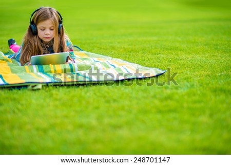 Girl Learning Language While Laying on the Park Green Field. Caucasian Girl with Wireless Headphones and Tablet. - stock photo