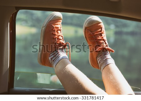 Girl legs in bright sneakers sticking out of the car - stock photo