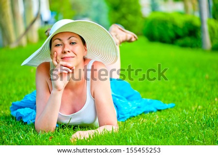 girl lies on a green lawn in a white hat - stock photo