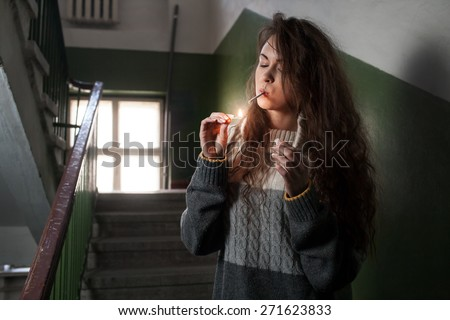 girl lights a cigarette in the stairwell - stock photo