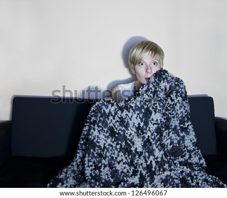 Girl listen to horror or suspense movie alone. Wrapped in a comfortable blanket, she is afraid of something happening. - stock photo