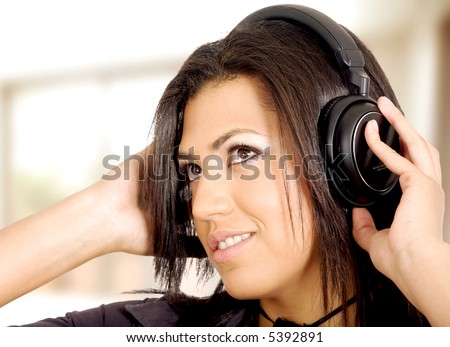 girl listening to music looking happy in her home - stock photo