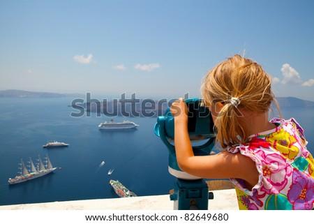 Girl looking at cruise ships with binoculars in Thira, Santorini, Greece - stock photo