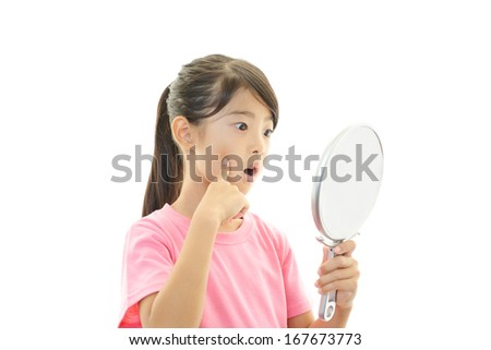 Girl looking at herself in a hand mirror - stock photo