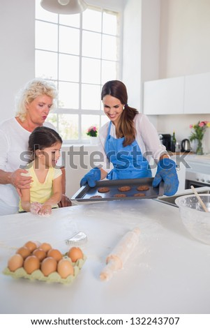 Girl looking at home-made cookies in the kitchen - stock photo