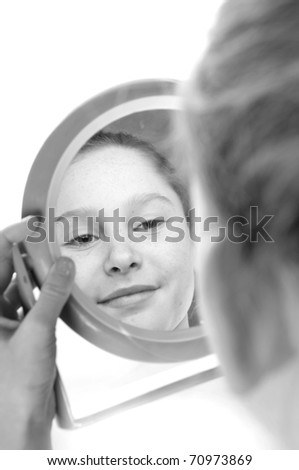 girl looking at reflection in mirror - stock photo