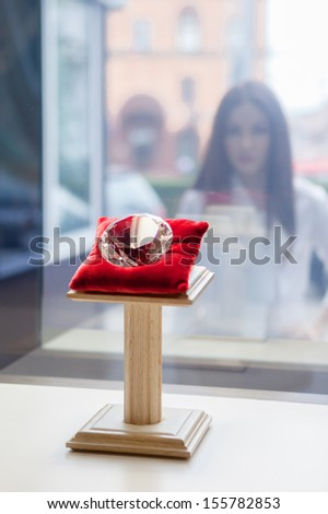 Girl looking at the diamond through the window at jeweler's shop. Concept of wealth and luxurious life - stock photo