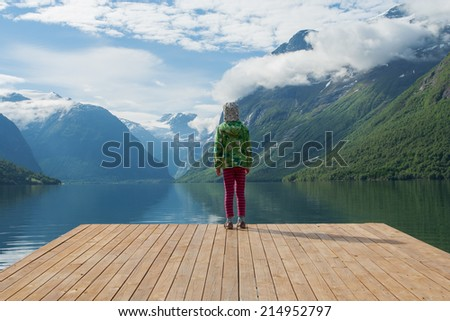 girl looking at the mountains and lake, norway  - stock photo