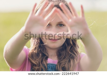 girl looking through a triangle shape of her hands - stock photo