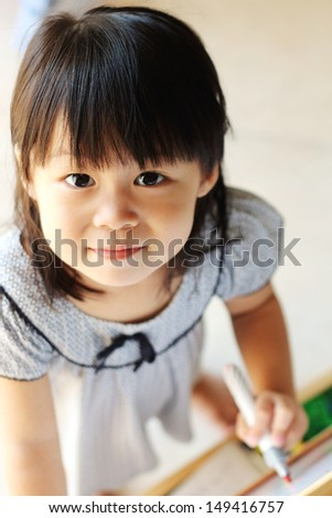 Girl looking up at camera while writing on board with pen in hand - stock photo