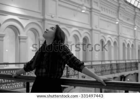 Girl looking up on the balcony in black and white - stock photo