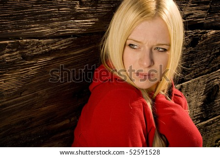 Girl looking worried sitting in front of old wall - stock photo