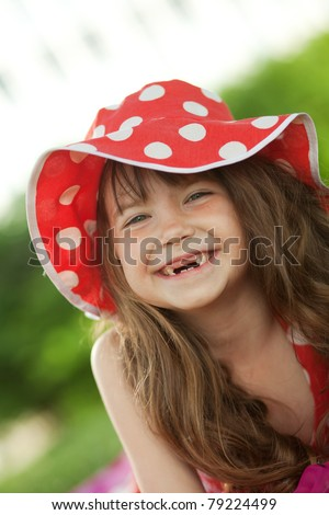girl looks at camera and smiles a toothless smile - stock photo
