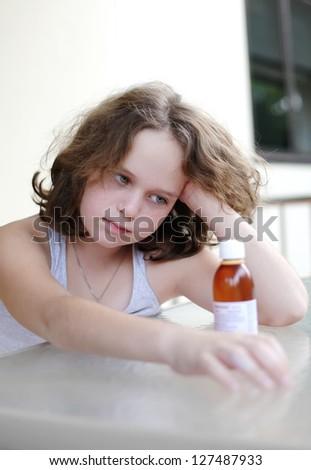 girl looks at medicine, she needs eat it - stock photo