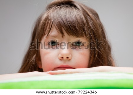 girl looks at the camera while lying on a towel - stock photo