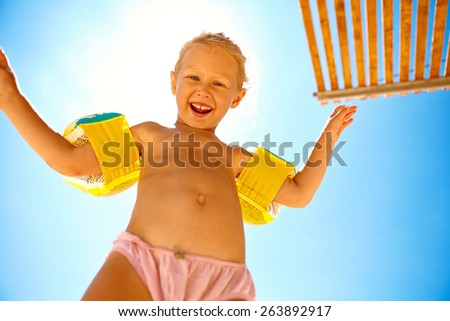 girl looks into the camera on the sunny beach over a blue sky - stock photo