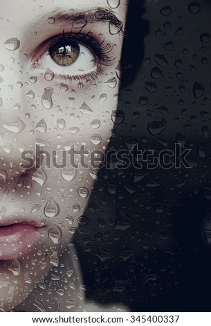 Girl looks out the window at the rain - stock photo