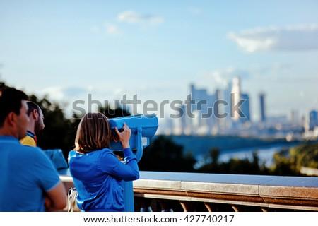 girl looks through binoculars at Moscow - stock photo