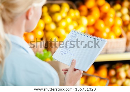 Girl looks through shopping list near the heap of fruits lying in the braided baskets in the shop - stock photo