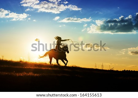 Girl loses hat while riding horse at sunset - stock photo