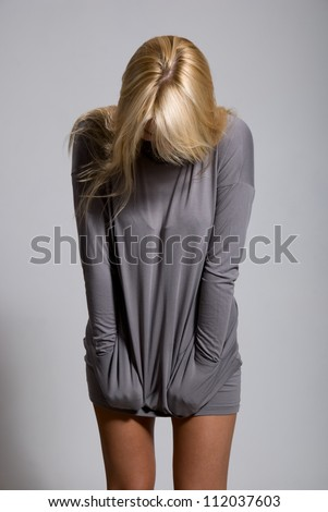 Girl low having inclined a head on a gray background - stock photo