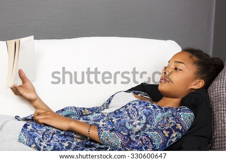 Girl lying in a couch reading a book. - stock photo