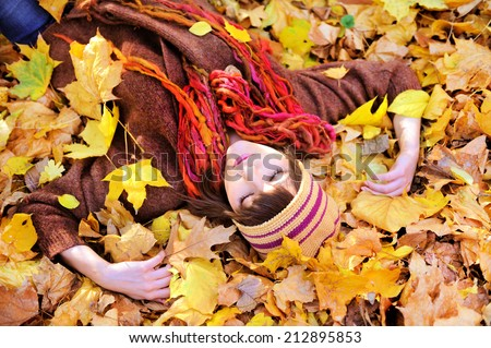 Girl lying in autumn leaves portrait, outdoor.  - stock photo
