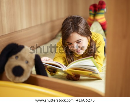 girl lying on bed and reading book. Copy space - stock photo