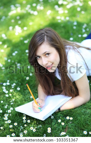 Girl lying on grass with workbook and pencil - stock photo