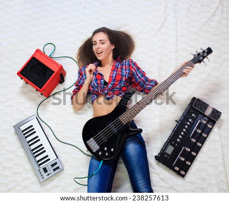 girl lying on the floor with bass guitar - stock photo