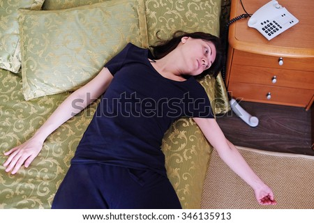 Girl lying unconscious next to the handset out - stock photo