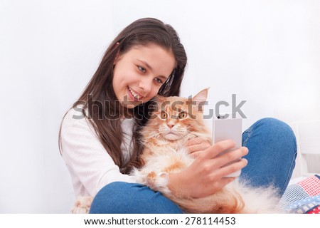 Girl making a photo with Maine Coon cat. Cat is very surprised - stock photo