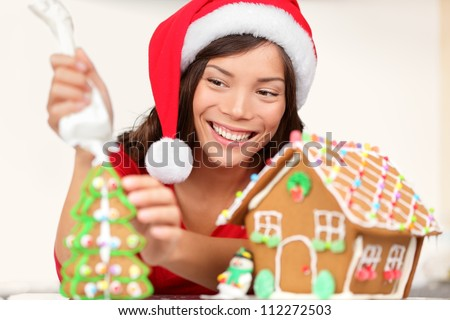 Girl making Christmas gingerbread house. Young woman in Christmas preparations putting icing on gingerbread house. Model wearing santa hat. - stock photo