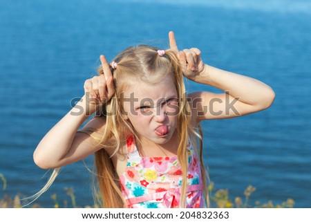 girl making face on seashore - stock photo