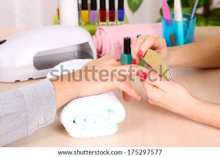Girl manicurist doing manicure for man in beauty salon  - stock photo