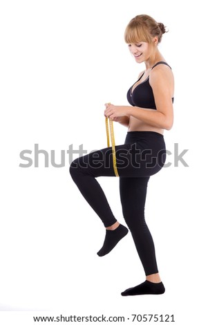 Girl measuring her thigh checking the result of diet, isolated on a white background - stock photo