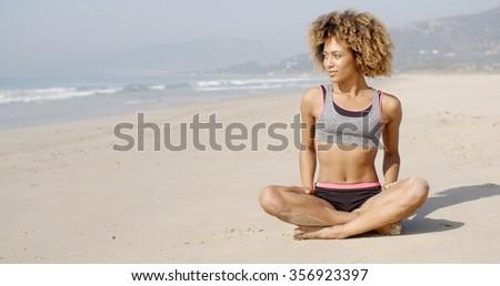 Girl meditating on the sea coast sitting in yoga position - stock photo