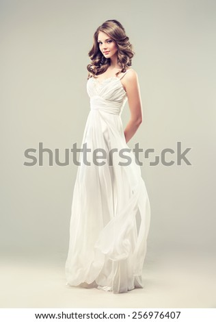 Girl model in a white wedding dress with elegant curly hairstyle - stock photo