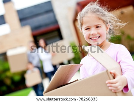 Girl moving house with his family and carrying boxes - stock photo
