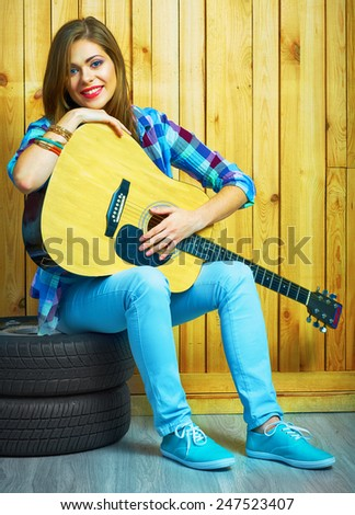 Girl musician play on acoustic guitar. Portrait of young model in hippie style. - stock photo